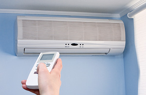 An AC Ductless Unit installed on a wall with remote control